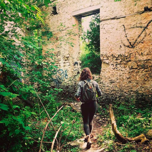 Jen Taylor walking amongst ruins overgrown by wildlife.